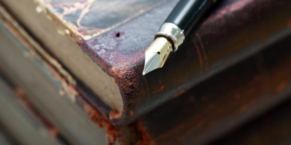 Closeup of fountain pen on stack of old books